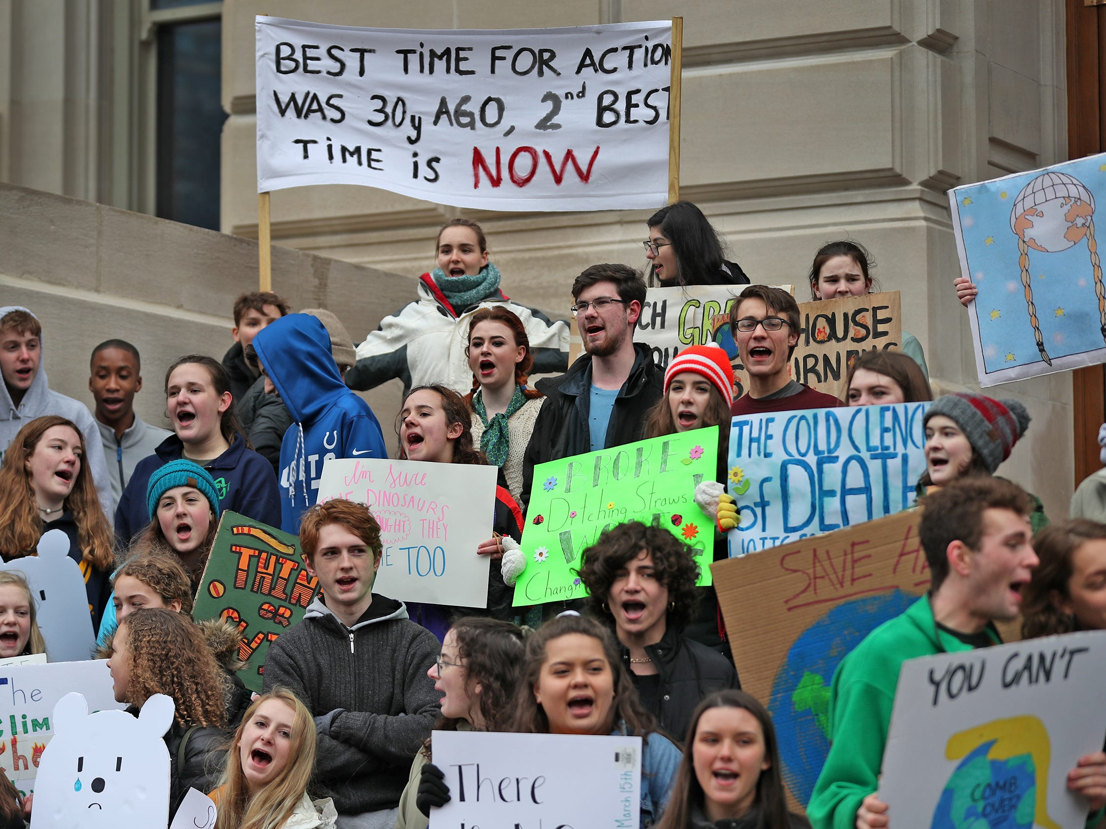 Students come together with a variety of signs during the Indiana part of the international Climate Strike, Friday, March 15, 2019, held outside the Indiana Statehouse.  Following in the footsteps of 16-year-old Swedish trailblazer, Greta Thunberg, students around the world are skipping school to protest government inaction on climate change.  The Indiana protest brought over 250 participants.