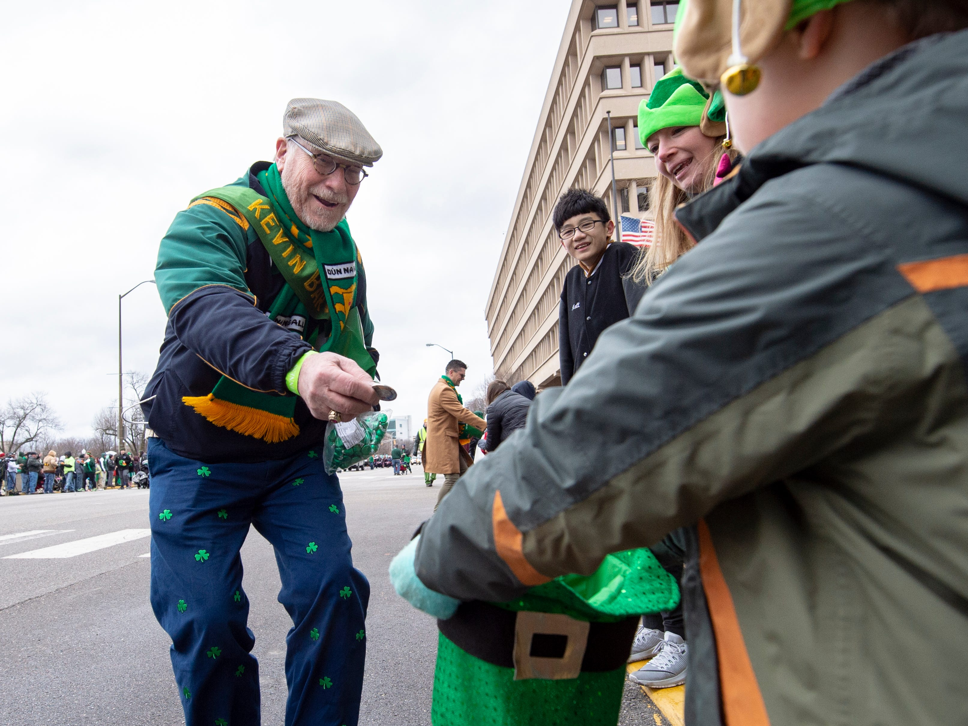The Grand Marshal of the parade, Kevin Murray, 2019 Irish Citizen of the Year, hands out coins during the parade. The 39th annual St. Patrick's Day Parade navigated the streets of Indianapolis, Friday, March 15, 2019.