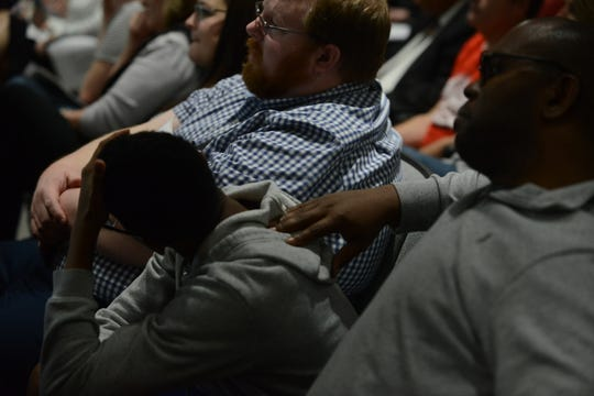 Kevin Hicks puts his hand on the back of his son, Kevin Hicks, Jr., as they listen to the school board deliberate the Ashport Road land option during the JMC school board meeting at Jackson City Hall on Thursday night.