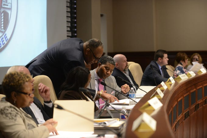"""JMCSS board member Morris Merriweather points something out to board member James """"Pete"""" Johnson before the start of the JMC school board meeting at Jackson City Hall on Thursday night."""