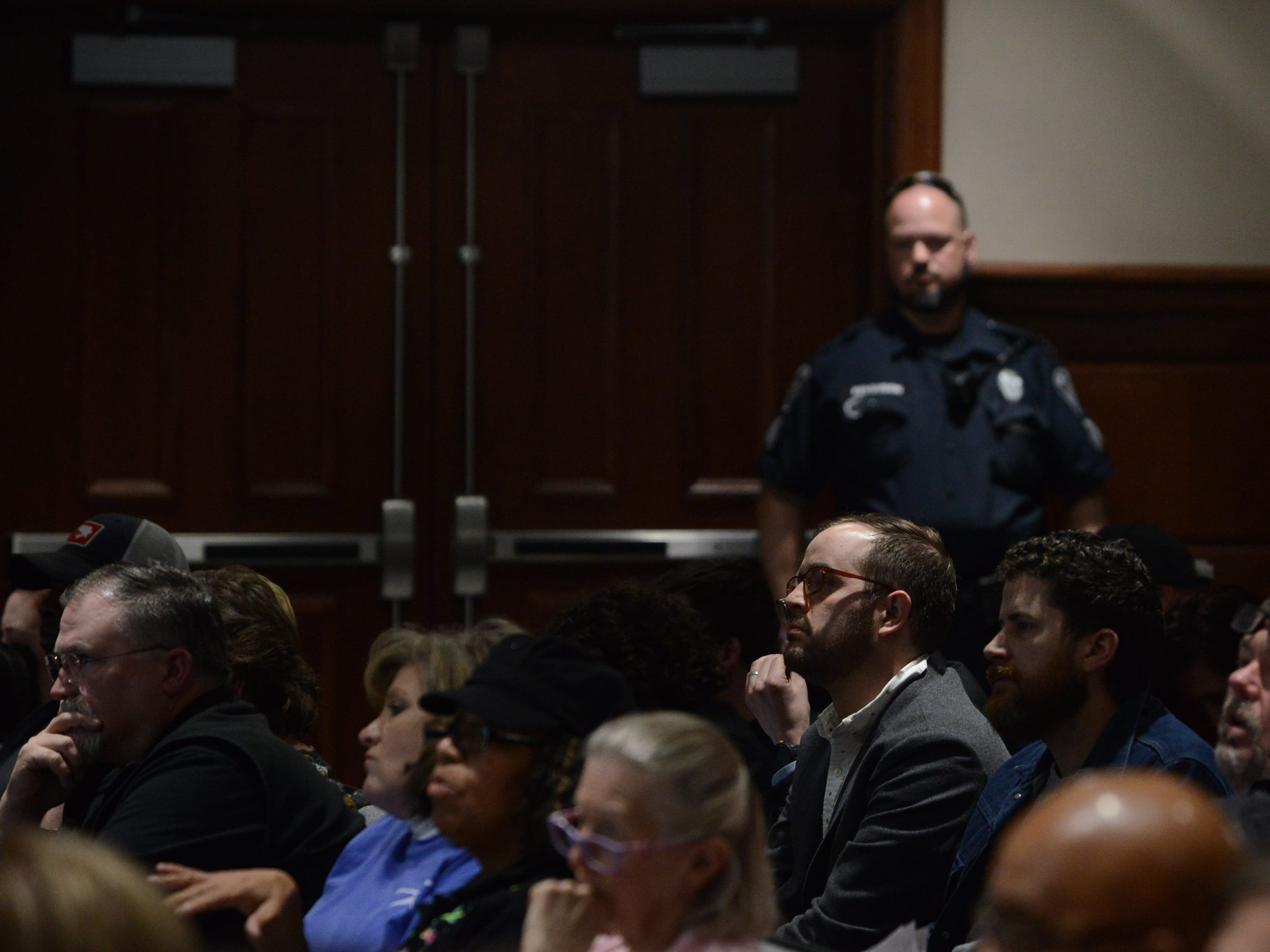 Audience members listen to board member deliberations while a Jackson Police Department officer stands near a meeting room door in the background at the JMC school board meeting at Jackson City Hall on Thursday night.