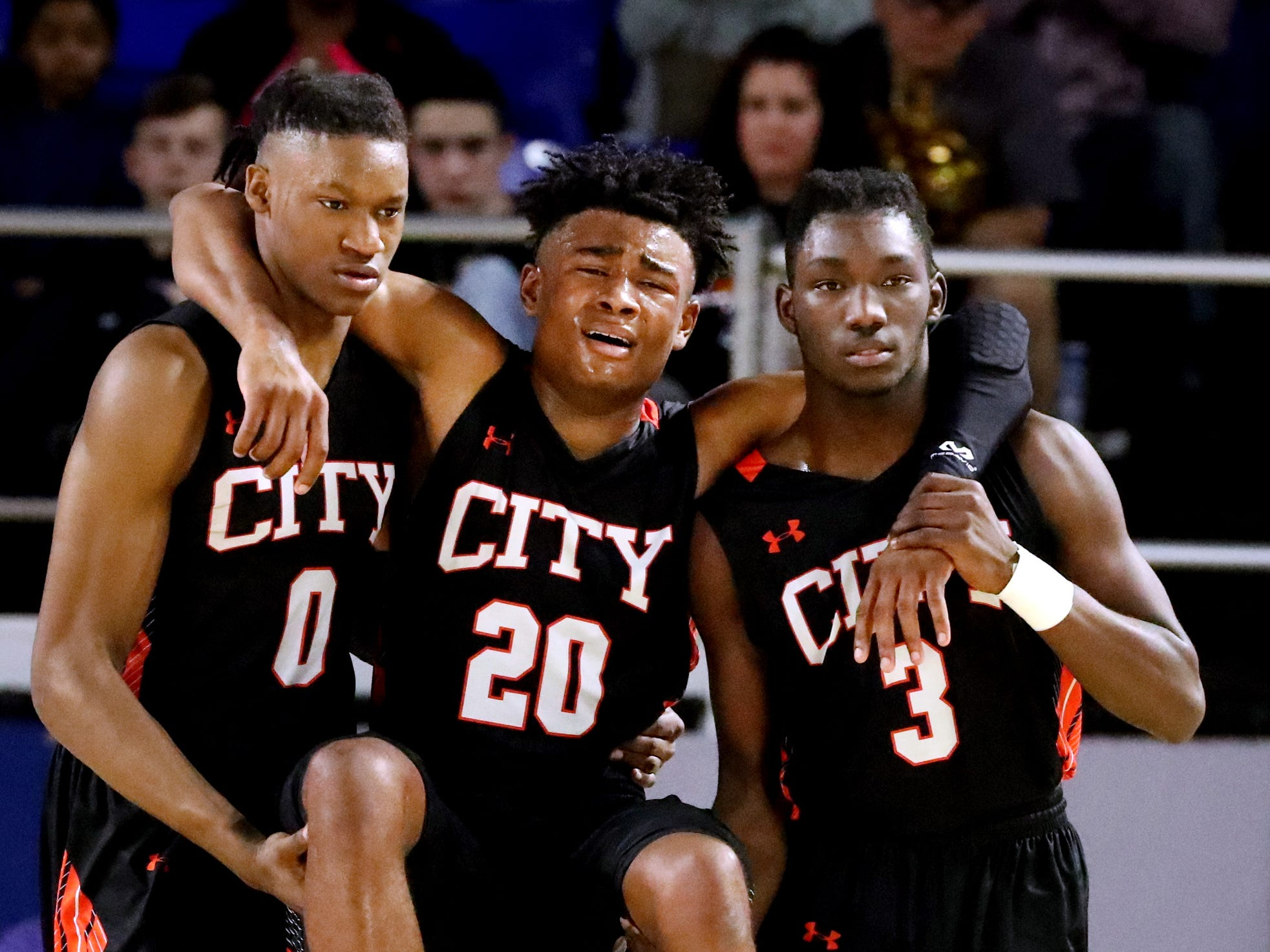 Fayetteville's Julius Dixon (0) and Jacious Clark (3) carry teammate Floyd Williams (20) off the court after he was injured in the first half of  the quarterfinal round of the TSSAA Class A Boys State Tournament, on Thursday, March 14, 2019, at Murphy Center in Murfreesboro, Tenn