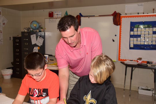 Stacy Aycock lends a helping hand to 10-year-olds Luke McManus (left) and Sam Brengle at Ball Camp Elementary School.