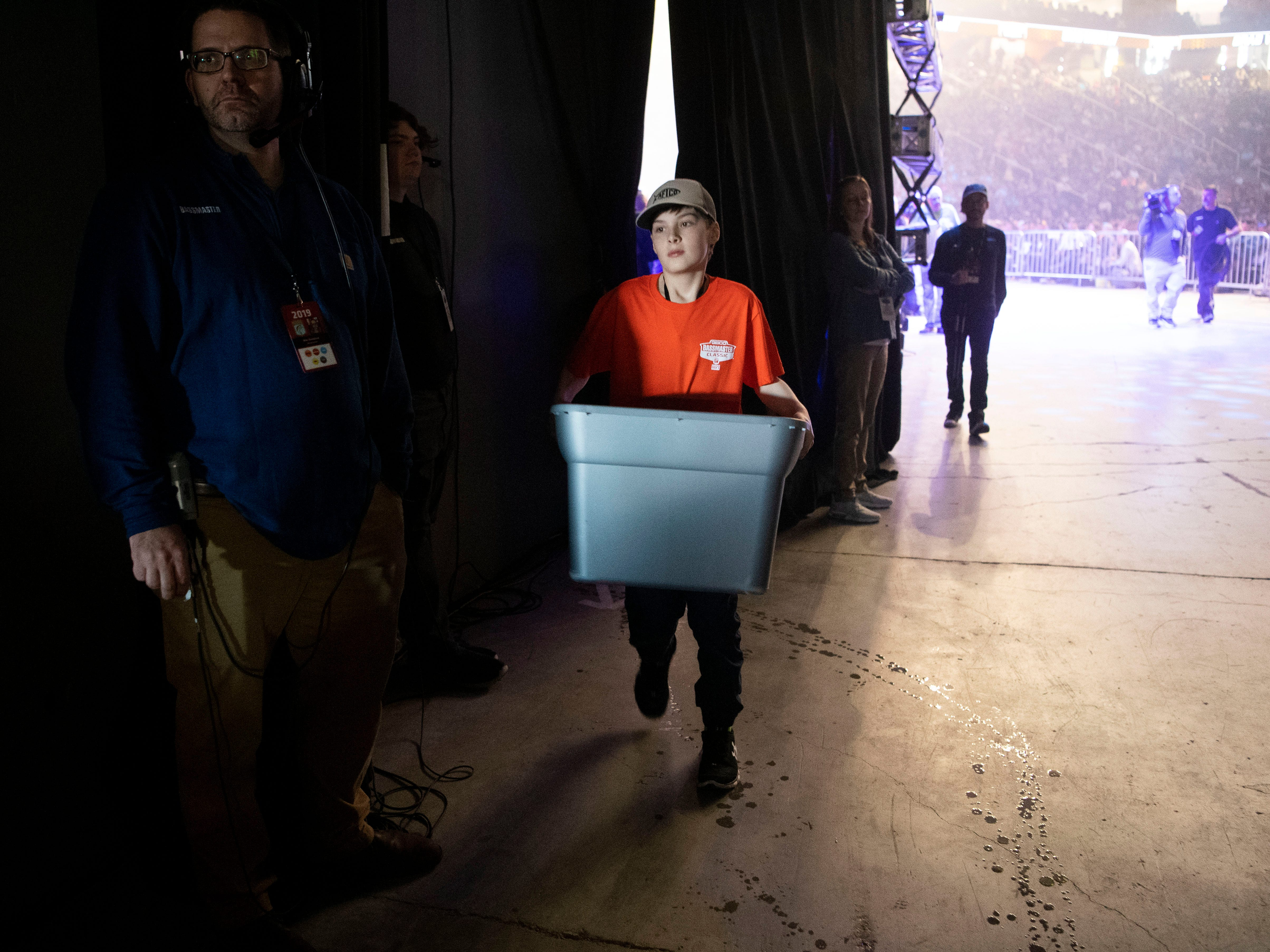 Trevor Barnucz of Ontario carries a container of bass to awaiting TWRA fisheries truck at the first day of weigh-ins during the Bassmaster Classic on Friday, March 15, 2019. Trevor is one of the many volunteers working under the coordination of B.A.S.S conservation director Gene Gilliland.