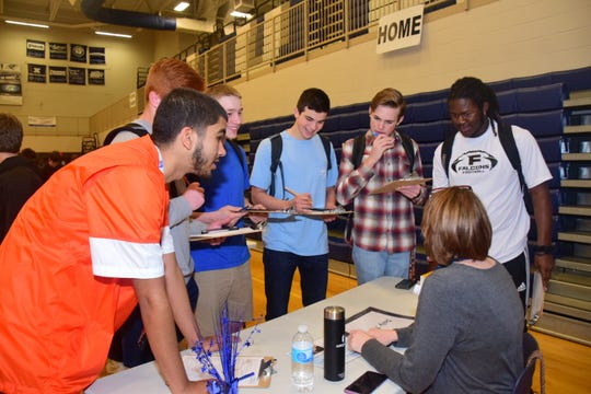 """PTSA secretary Laura Feldman helps students decide how much they'll spend on treats like coffee, bottled water, and lunches during """"My Amazing Life"""" held at Hardin Valley Academy Thursday, March 14. From left are Jaston Smith, Luke Filipkowski, Kyle Tate, Harper Haulk, Ian Holt and Jaylee Moore."""