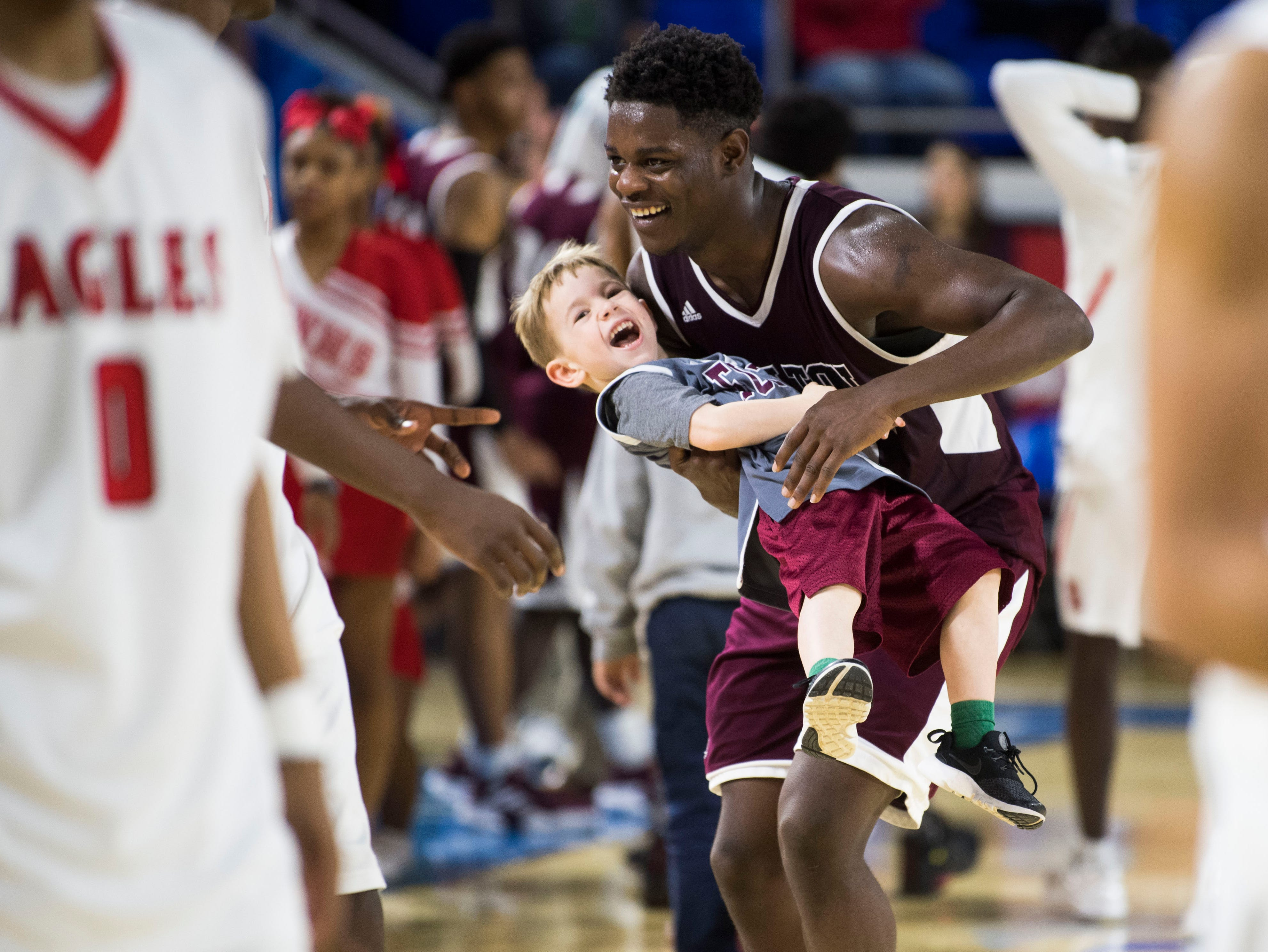 Fulton's Deshawn Page (32) picks up assistant coach Jonathan Cox's son Tatum Cox, 4, while celebrating a win after a TSSAA AA state semifinal game between East Nashville and Fulton at the Murphy Center in Murfreesboro, Friday, March 15, 2019. Fulton defeated East Nashville 66-55.
