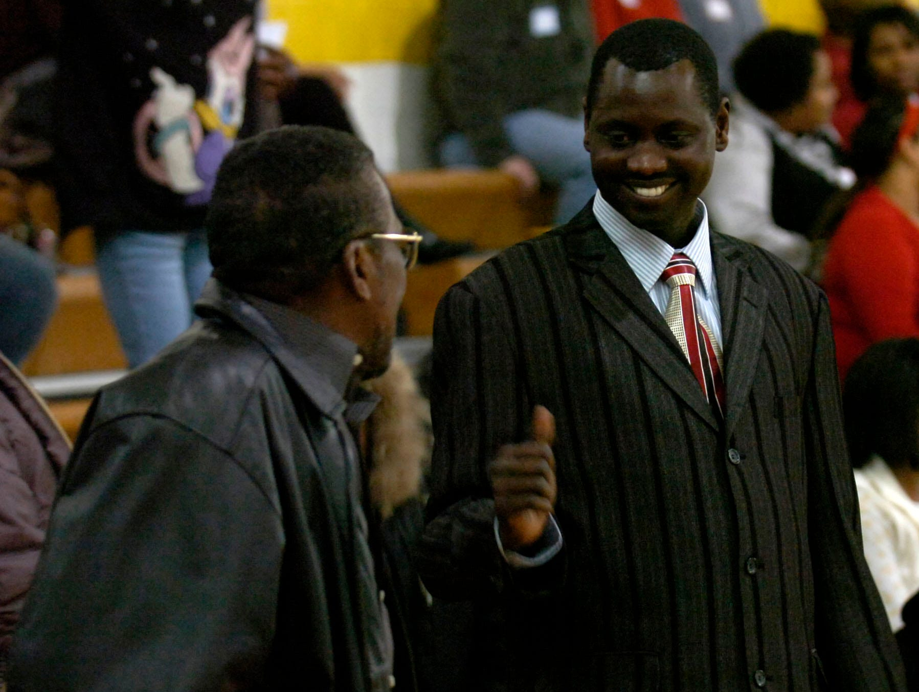 "Victor Chol, right, a Sudanese immigrant featured in the ""Lost Boys of Sudan"" documentary motions to Alfred Williams, one of the ""Clinton 12"" after speaking during a youth symposium in celebration of Martin Luther King Jr. The event was held at Vine Middle Performing Arts and Sciences Magnet School on Saturday."