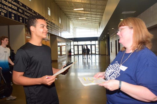 """Junior Cameron Smith chooses his career and is given a salary by volunteer Amy Bush at """"My Amazing Life"""" held at Hardin Valley Academy Thursday, March 14."""