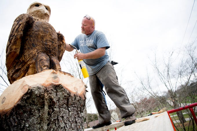 Jeff Banning, owner of Wood Carved Creations, uses a blowtorch to darken a bald eagle he carved atop a tree stump at a home on Washington Pike in East Knox County on Thursday, March 14, 2019. Banning has been following his passion for wood carving for two years and this was his third outdoor commissioned work. The homeowner hired Banning to carve a monument to honor military veterans and the many law enforcement officers that live in the area, as well as to surprise her boyfriend who will be returning from Fort Campbell later this month.