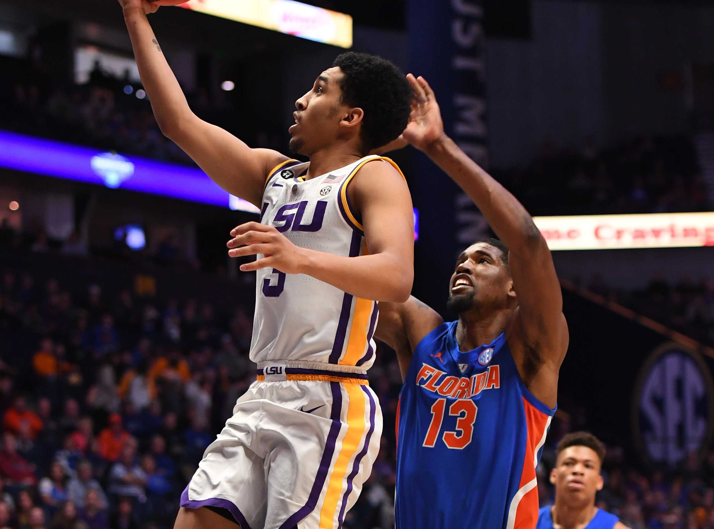 Mar 15, 2019; Nashville, TN, USA; LSU Tigers guard Tremont Waters (3) scores past Florida Gators center Kevarrius Hayes (13) during the first half of the SEC conference tournament at Bridgestone Arena. Mandatory Credit: Christopher Hanewinckel-USA TODAY Sports
