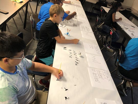 Students practice drawing Roman letters during a Saturday camp led by seniors at David Thibodaux STEM Magnet Academy this year.