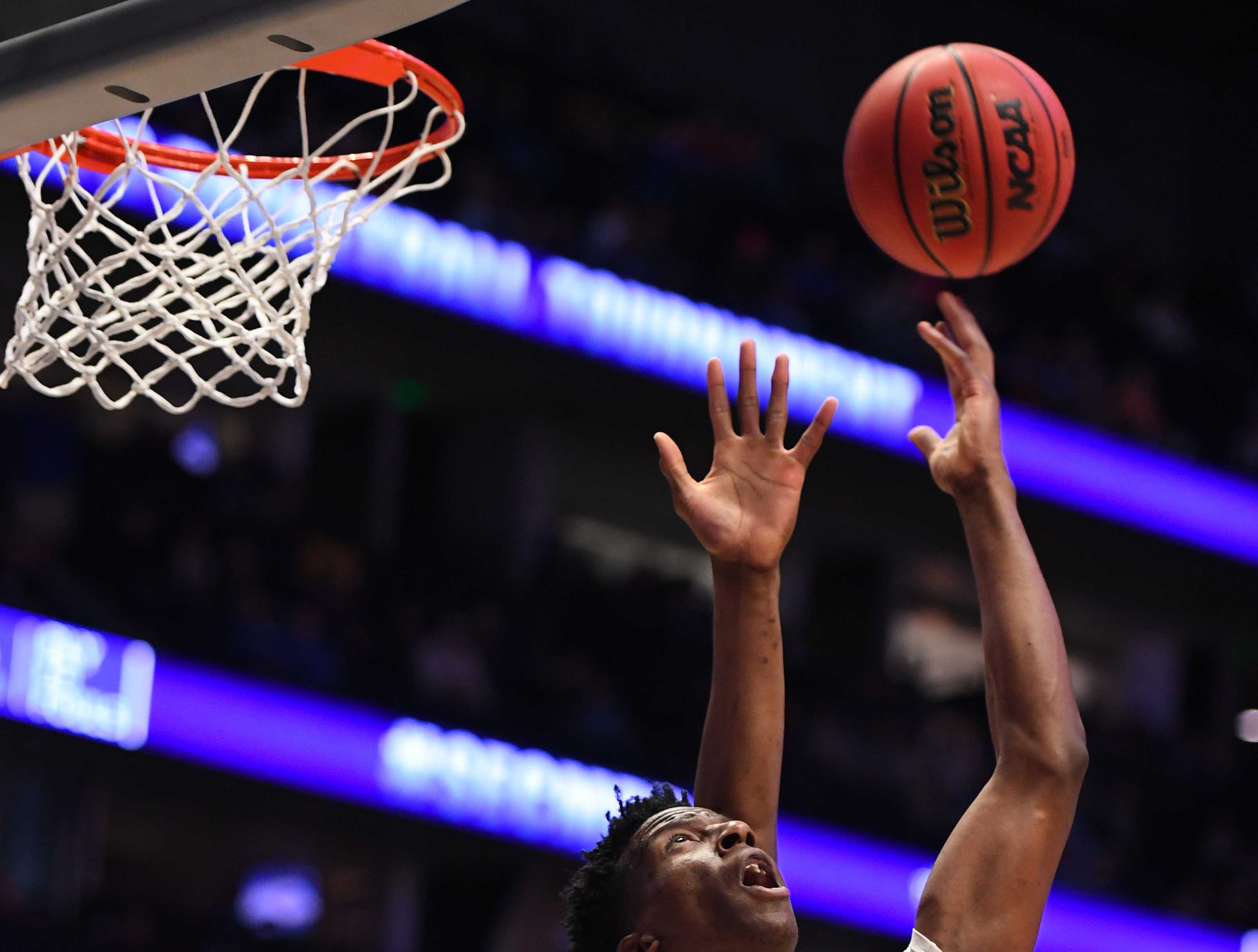 Mar 15, 2019; Nashville, TN, USA; LSU Tigers forward Kavell Bigby-Williams (11) makes a basket as he is defended by Florida Gators center Kevarrius Hayes (13) during the first half of the SEC conference tournament at Bridgestone Arena. Mandatory Credit: Christopher Hanewinckel-USA TODAY Sports