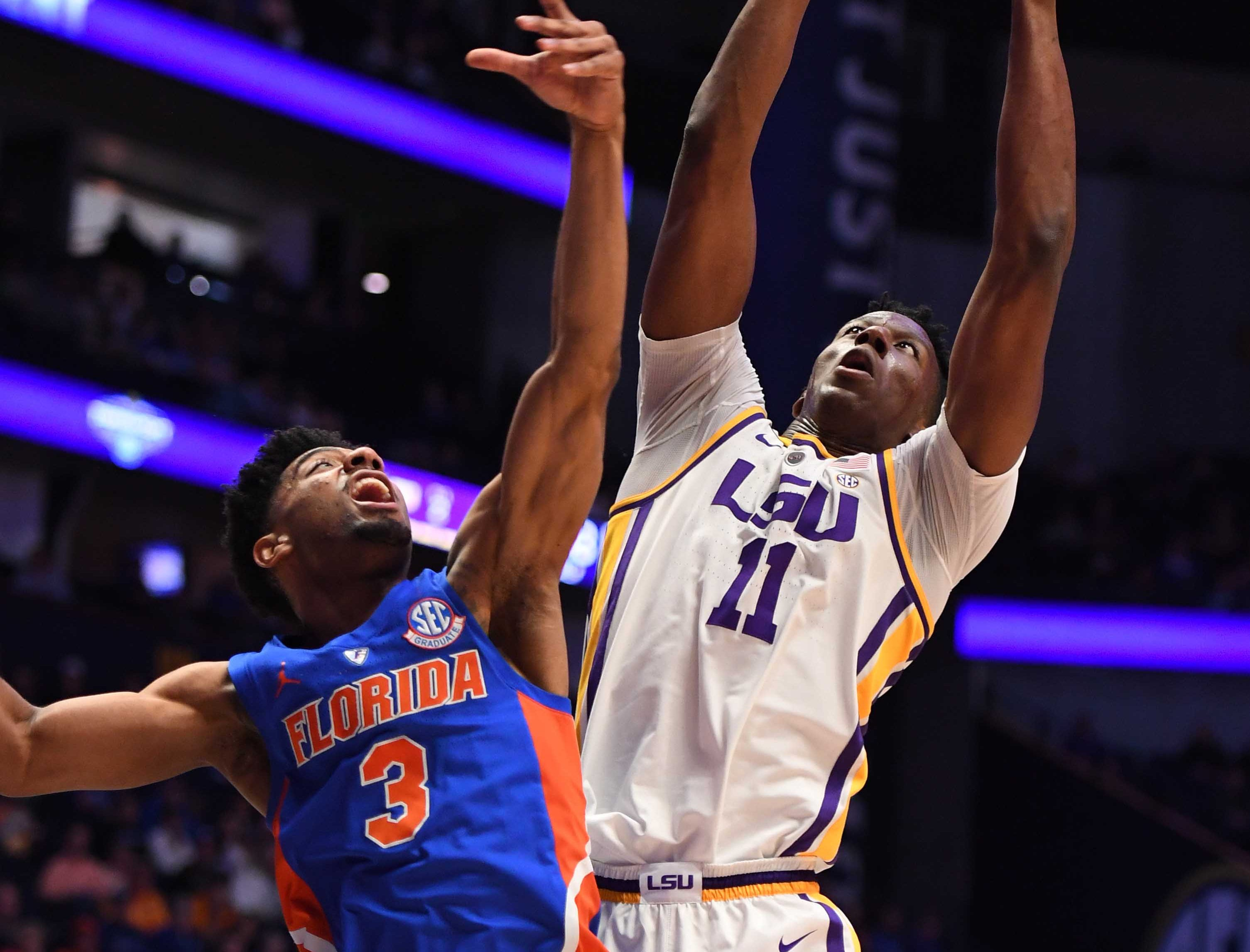 Mar 15, 2019; Nashville, TN, USA; LSU Tigers forward Kavell Bigby-Williams (11) grabs a rebound over Florida Gators guard Jalen Hudson (3) during the first half of the SEC conference tournament at Bridgestone Arena. Mandatory Credit: Christopher Hanewinckel-USA TODAY Sports