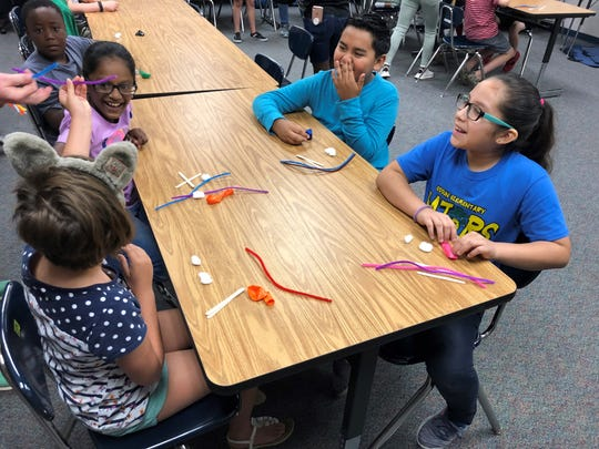 Students create trebuchets out of pipe cleaners to launch cotton balls during a Saturday camp led by seniors at David Thibodaux STEM Magnet Academy this year.