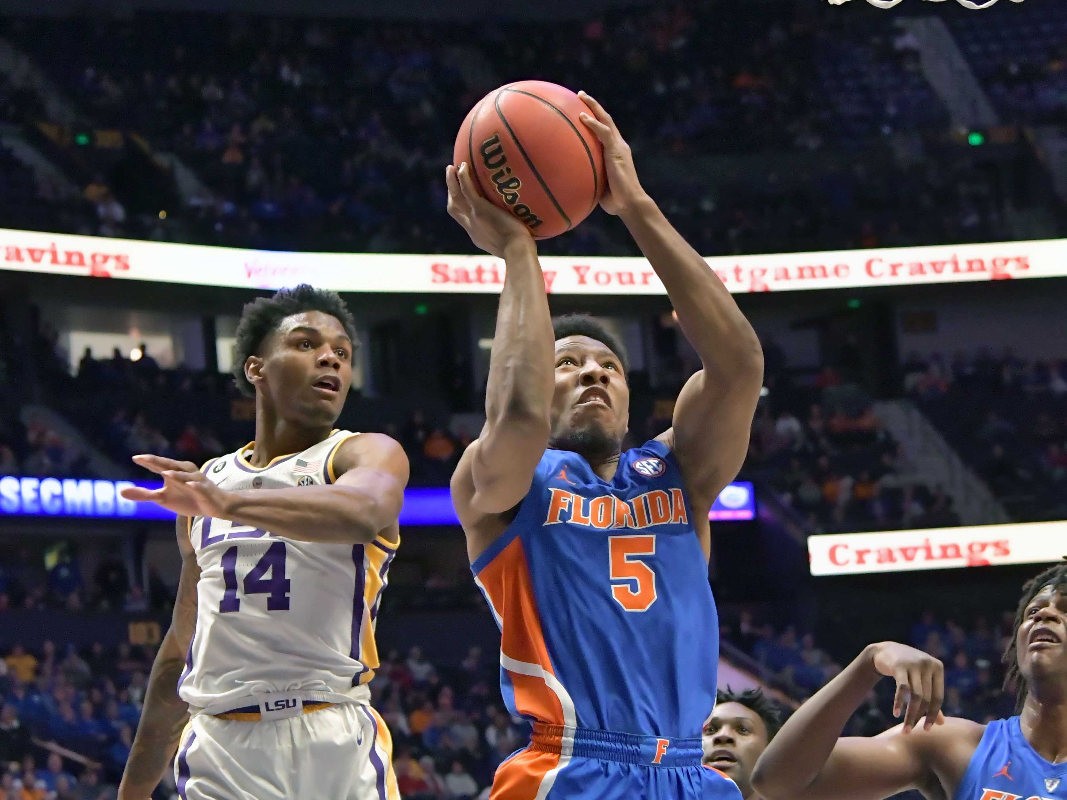 Mar 15, 2019; Nashville, TN, USA; Florida Gators guard KeVaughn Allen (5) shoots against LSU Tigers guard Marlon Taylor (14) during the first half of game seven in the SEC conference tournament at Bridgestone Arena. Mandatory Credit: Jim Brown-USA TODAY Sports