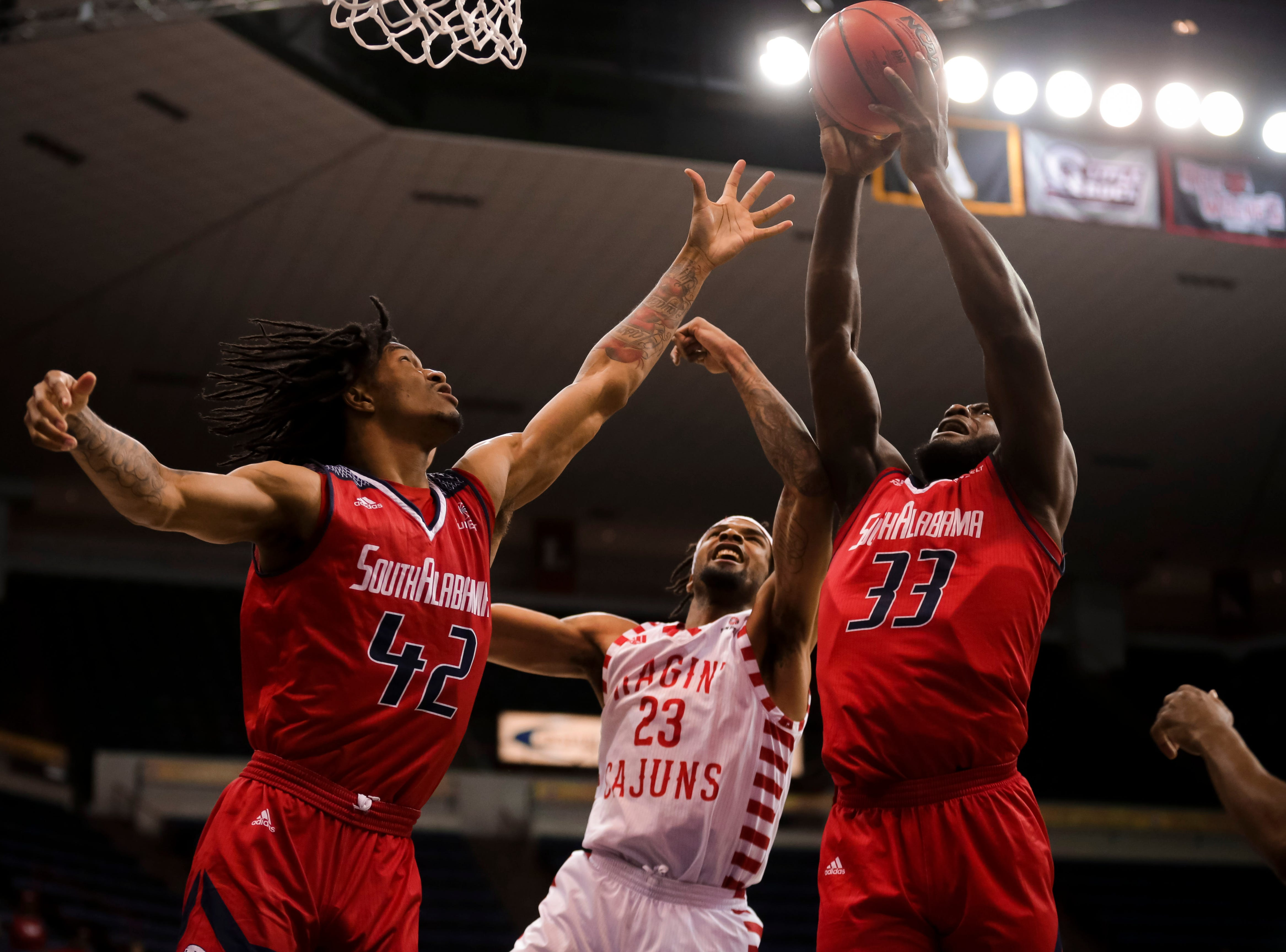 UL's Jakeenan Gant tries to defend against a South Alabama shooter. The Ragin' Cajuns fell to South Alabama, 70-69, on Thursday at the Sun Belt Men's Basketball Championship in New Orleans.