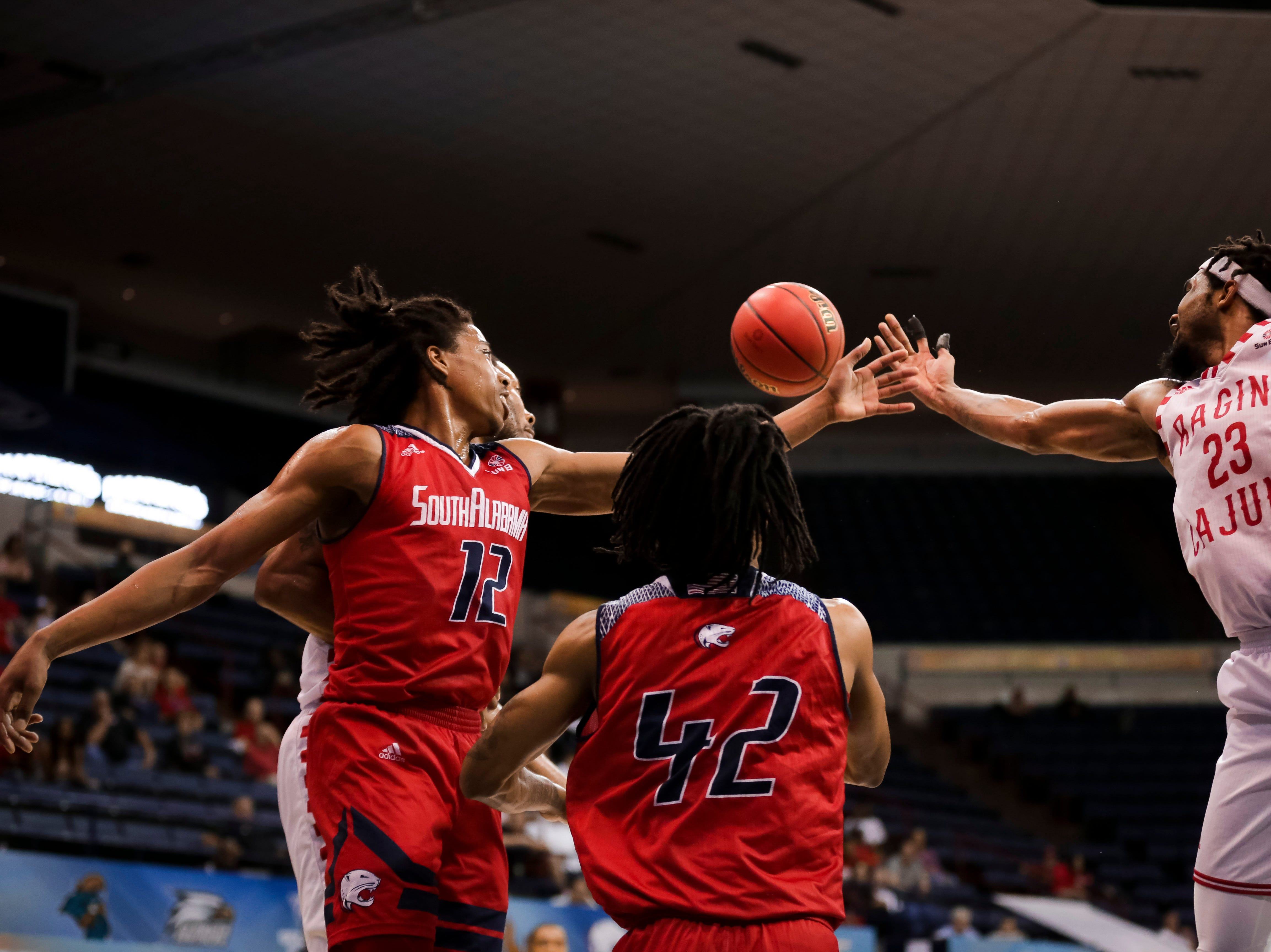 UL's Jakeenan Gant (right) fights for the ball, as the Ragin' Cajuns fell to South Alabama, 70-69, on Thursday at the Sun Belt Men's Basketball Championship in New Orleans.