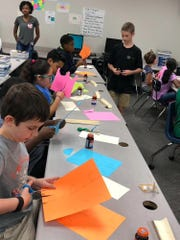 Students make aqueducts out of construction paper before running water through them as a test. The activity was part of David Thibodaux STEM Magnet Academy's free Saturday camps hosted four times this school year.