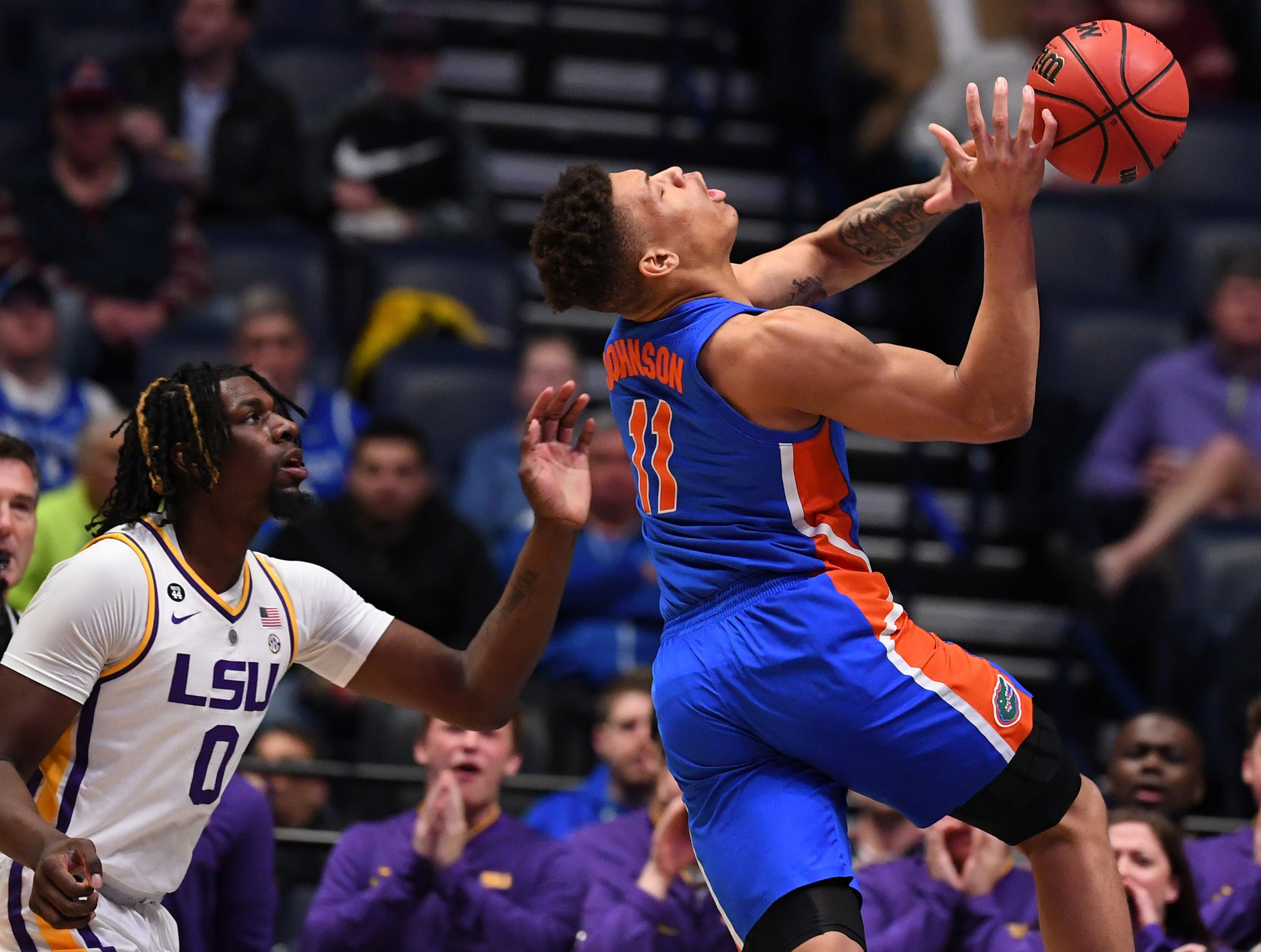 Mar 15, 2019; Nashville, TN, USA; Florida Gators forward Keyontae Johnson (11) is fouled by LSU Tigers forward Naz Reid (0) while shooting the ball during the first half of the SEC conference tournament at Bridgestone Arena. Mandatory Credit: Christopher Hanewinckel-USA TODAY Sports
