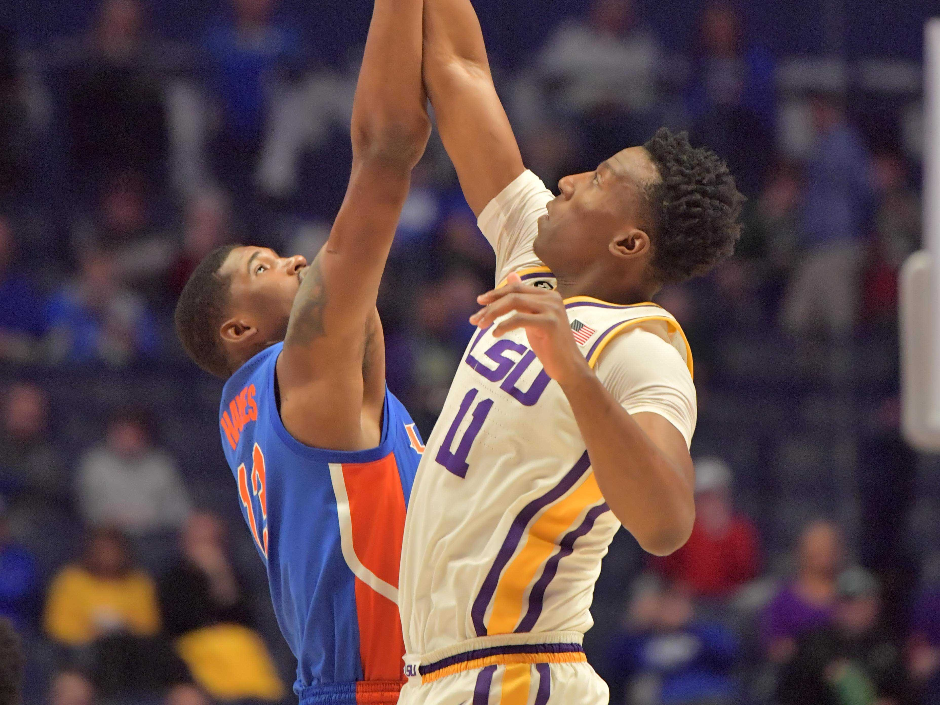 Mar 15, 2019; Nashville, TN, USA; LSU Tigers forward Kavell Bigby-Williams (11) reaches or the jump ball against Florida Gators center Kevarrius Hayes (13) during the first half of game seven in the SEC conference tournament at Bridgestone Arena. Mandatory Credit: Jim Brown-USA TODAY Sports