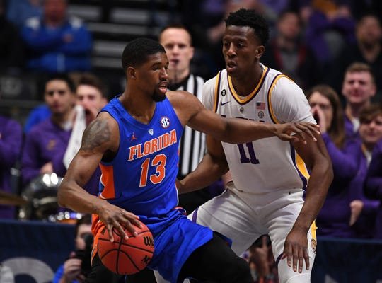 Mar 15, 2019; Nashville, TN, USA; Florida Gators center Kevarrius Hayes (13) controls the ball in front of LSU Tigers forward Kavell Bigby-Williams (11) during the first half of the SEC conference tournament at Bridgestone Arena. Mandatory Credit: Christopher Hanewinckel-USA TODAY Sports