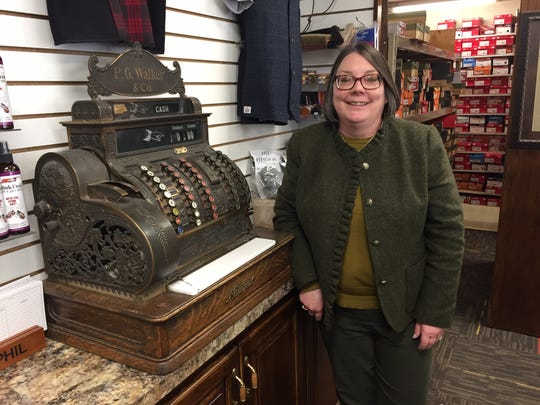 Walker's Shoe Center sixth-generation owner Melissa Walker stands beside the vintage cash register at the 737 E. Main St. business.