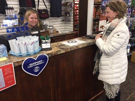 Kristi Scheffler, wife of Mayor David Scheffler, makes a purchase at Walker's Shoe Center recently. Behind the counter is employee Logan Burkhart.