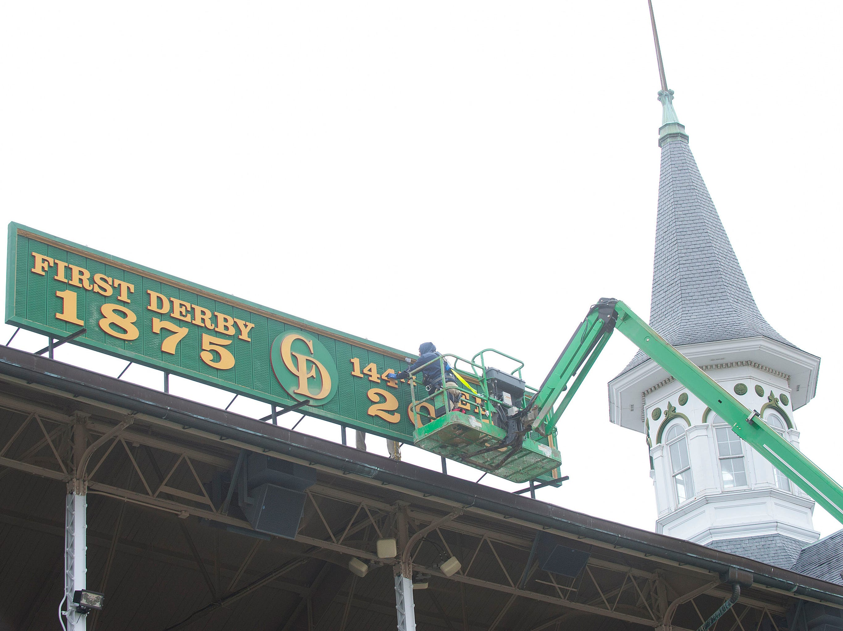Churchill Downs sign shop worker Todd Herl removes the number 4 as he prepares to replace it with the number 5, on a sign hung between the twin spires that reflects the year's running of the Kentucky Derby.  