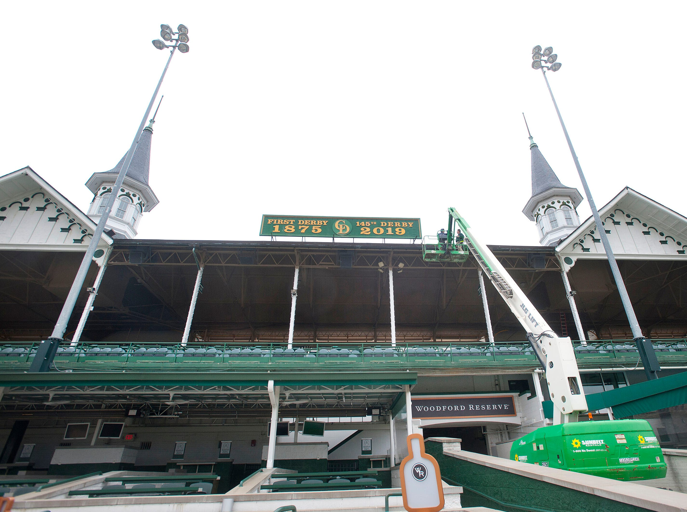 Churchill Downs sign shop workers Todd Herl and Bryan Theising use a scissor lift to get down from the sign hung between the twin spires that reflects this year's running of the Kentucky Derby.  