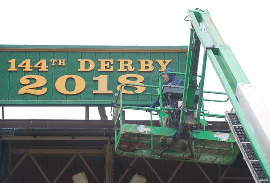 Churchill Downs sign shop worker Todd Herl positions a scissor lift to get to a sign hung between the twin spires that reflects the year's running of the Kentucky Derby.  15 March 2019
