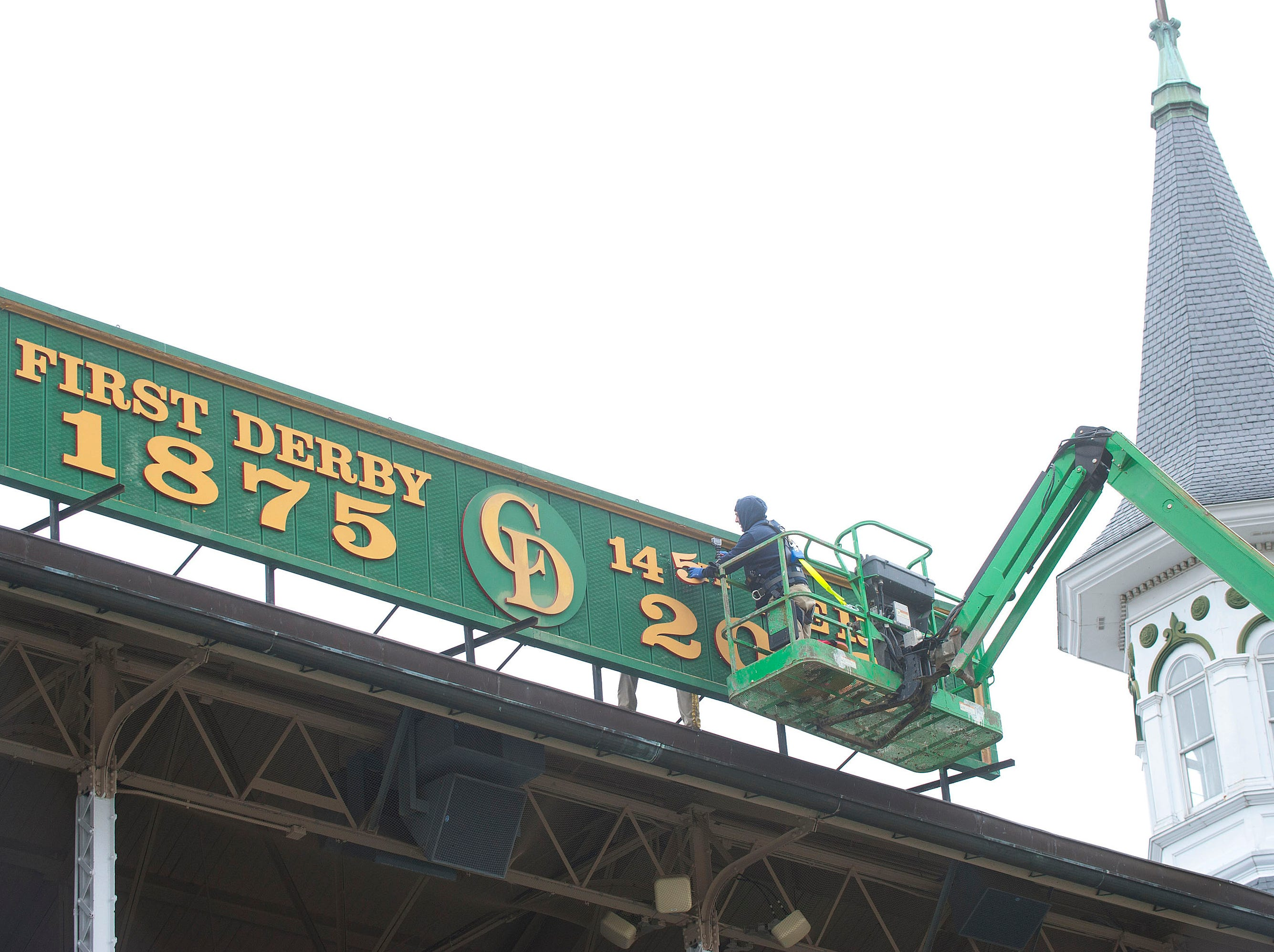 Churchill Downs sign shop worker Todd Herl positions the number 5, on a sign hung between the twin spires that reflects this year's running of the Kentucky Derby.  