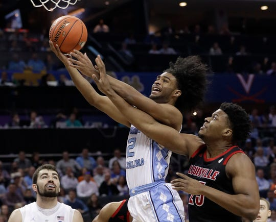 UNC's Coby White (2) drives past Louisville's Steven Enoch in the first half of Thursday's ACC Tournament game.