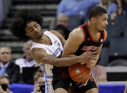 North Carolina's Coby White, left, reaches across to strip the ball from Louisville's Christen Cunningham, right, during the first half of an NCAA college basketball game in the Atlantic Coast Conference tournament in Charlotte, N.C., Thursday, March 14, 2019.