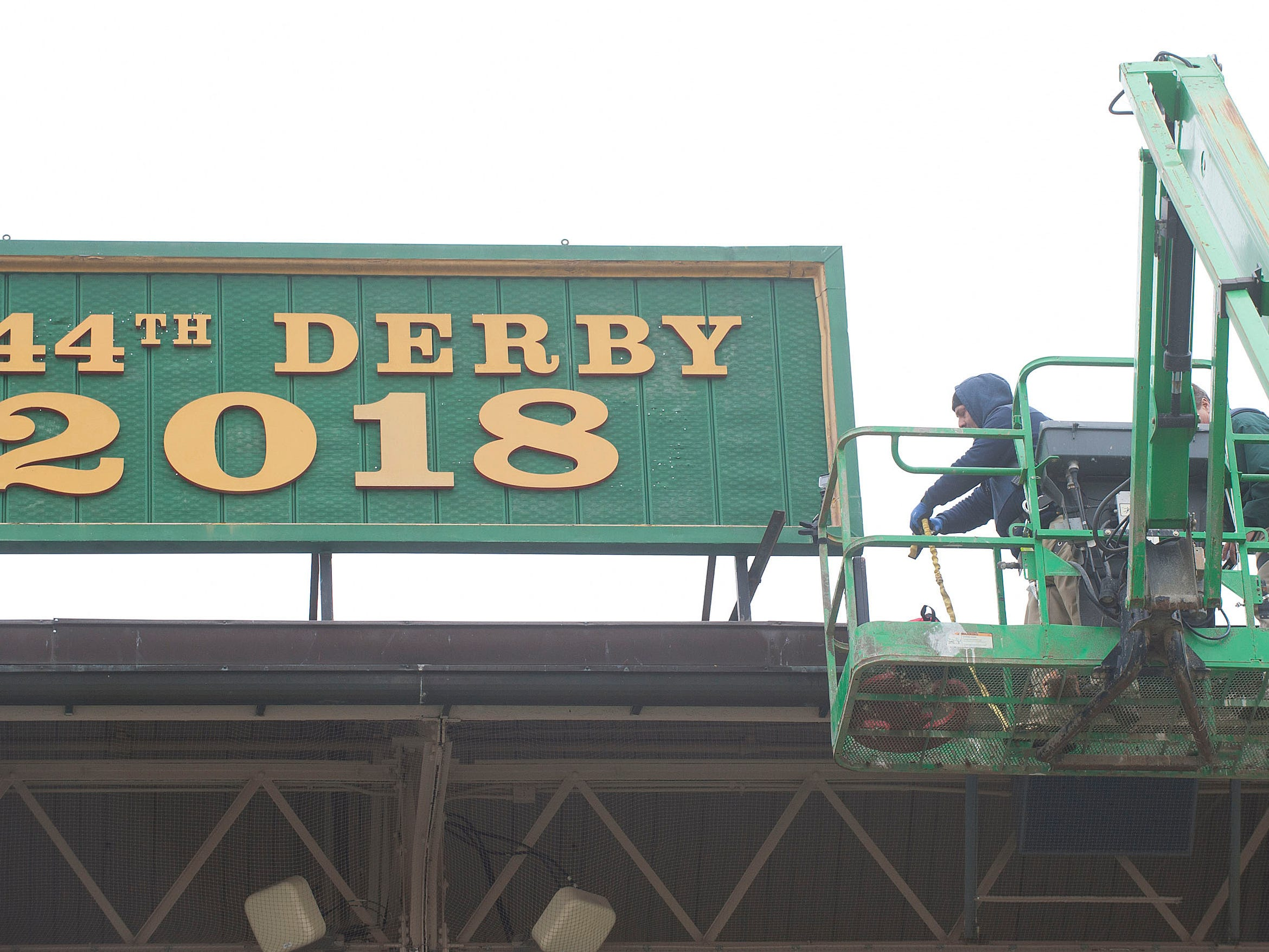 Churchill Downs sign shop worker Todd Herl positions a scissor lift to get to a sign hung between the twin spires that reflects the year's running of the Kentucky Derby.  