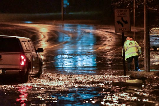A stranded car can be seen in the background as a worker with the City of Lansing heads thru water to clean a drain where flooding occurred over Edgewood Blvd. just east of Martin Luther King Blvd. early Thursday, March 14, 2019.