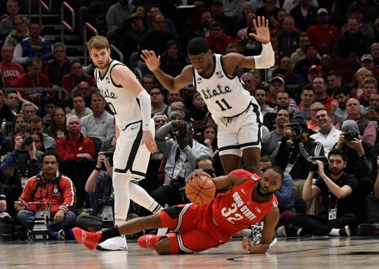 Ohio State Buckeyes guard Keyshawn Woods (32) is fouled by Michigan State Spartans forward Aaron Henry (11) during the second half in the Big Ten conference tournament at United Center.