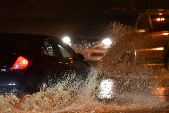 Cars try to drive thru an area where flooding over Edgewood Blvd. just east of Martin Luther King Blvd. Thursday, March 14, 2019.