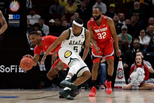 Ohio State's Luther Muhammad (1) and Michigan State's Cassius Winston (5) battle for a loose ball during the first half of an NCAA college basketball game in the quarterfinals of the Big Ten Conference tournament, Friday, March 15, 2019, in Chicago.