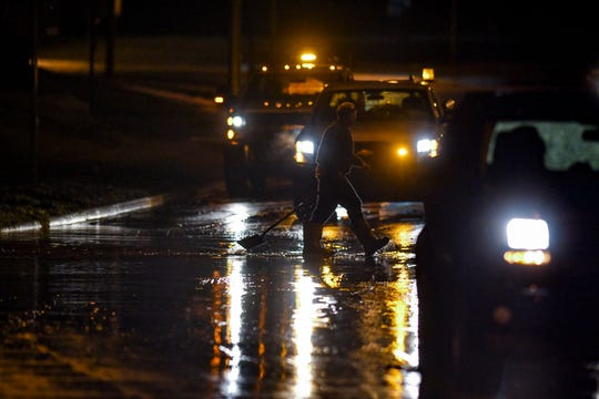A worker with the City of Lansing heads through water on the road to clean a drain on Edgewood Boulevard, just east of Martin Luther King Jr. Boulevard, on Thursday, March 14, 2019.