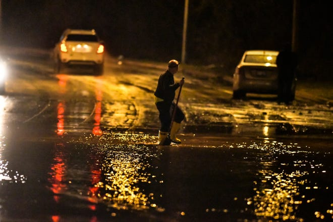 A stranded motorist can be seen in the background as a worker with the City of Lansing heads thru water to clean a drain where flooding over Edgewood Blvd. just east of Martin Luther King Blvd. occurred early Thursday, March 14, 2019.
