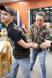 Braxton Heins and his sister practice handcuffing techniques during the first Mishicot Public Safety Cadets meeting in February.