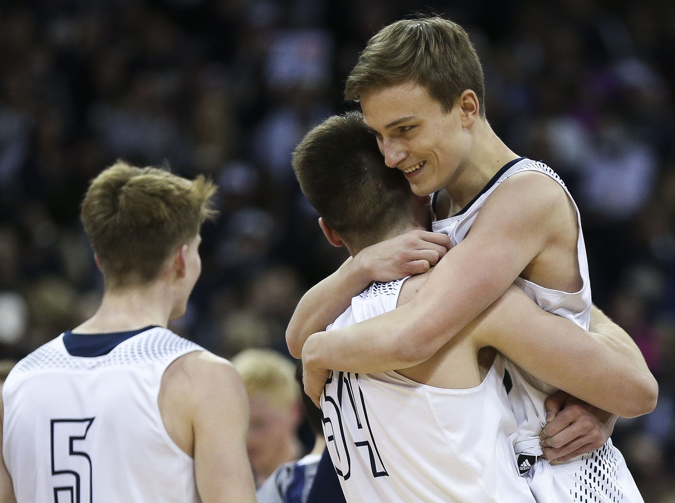 Columbus Catholic High School's Jarred Mandel (54) lifts up Tom Nystrom (right) on the court after a Division 5 boys basketball state semifinal on Friday, March 15, 2019, at the Kohl Center in Madison, Wis. Nystrom hit a game-winning 3-pointer at the buzzer to give the Dons a 69-66 victory over Bangor High School. Tork Mason/USA TODAY NETWORK-Wisconsin
