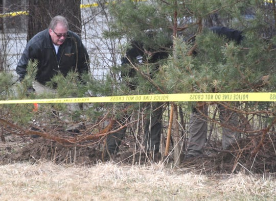 Richland County Coroner's Office investigator  Bob Ball watches as Mansfield Police dig near Floral Court on Friday afternoon.
