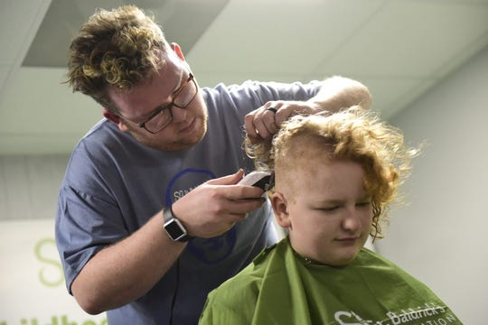 Levi Short shaves away rows of hair from the head of Hayden White, 13, of Shelby, during the St. Baldrick's fundraiser Friday in Shelby.