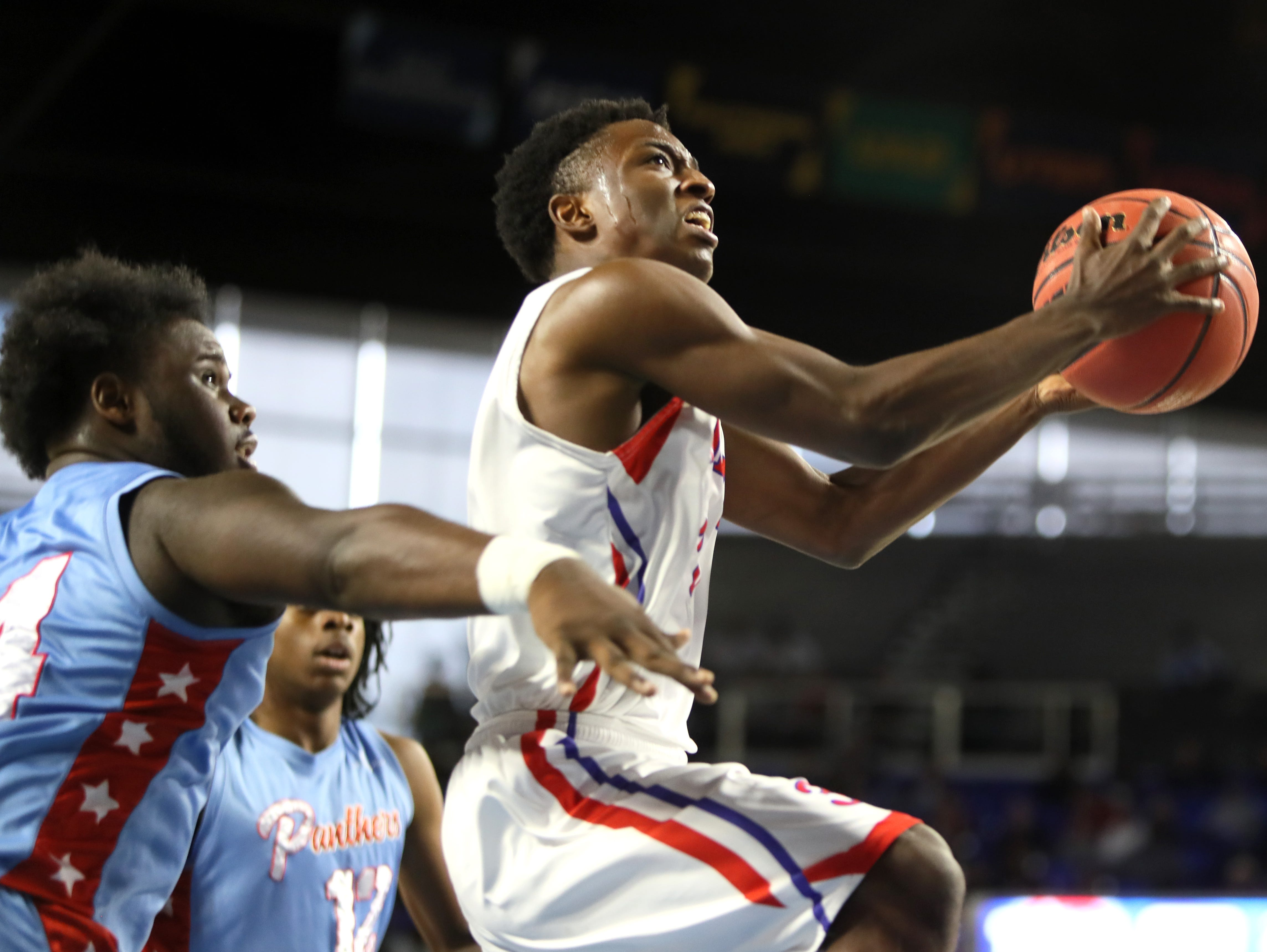 Wooddale's Alvin Miles lays the ball up past Brainerd's Ciante Chaney during the Class AA boys basketball state semifinal at the Murphy Center in Murfreesboro, Tenn. on Thursday, March 14, 2019.