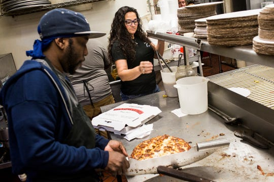 Dewana Ishee, right, helps out in the kitchen as Will Rose, left, cuts a pizza at Broadway Pizza's original location on Broad Avenue.