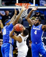 Memphis teammates Mike Parks Jr. (left) and Raynere Thornton (right) apply pressure to the shot of UCF guard BJ Taylor (middle) during action in their quarterfinal round AAC Tournament game at the FedExForum, Friday, March 15, 2019.