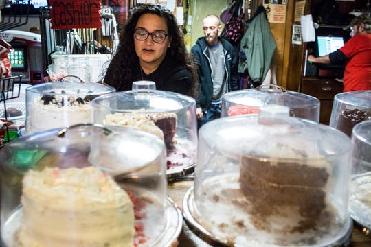 Dewana Ishee sets a cake out on display while working at Broadway Pizza's original location on Broad Avenue.