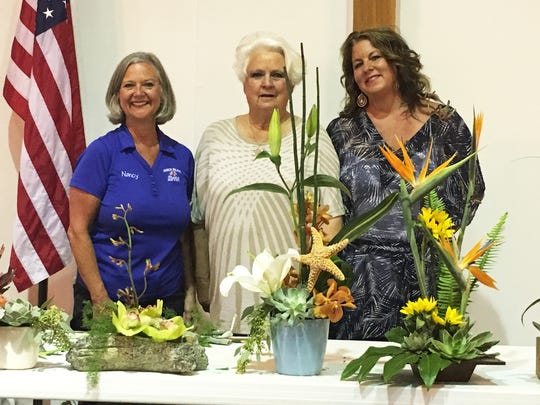 Nancy Carrington, Sandy Wallen, Annemarie Dalfonso show floral arrangements.
