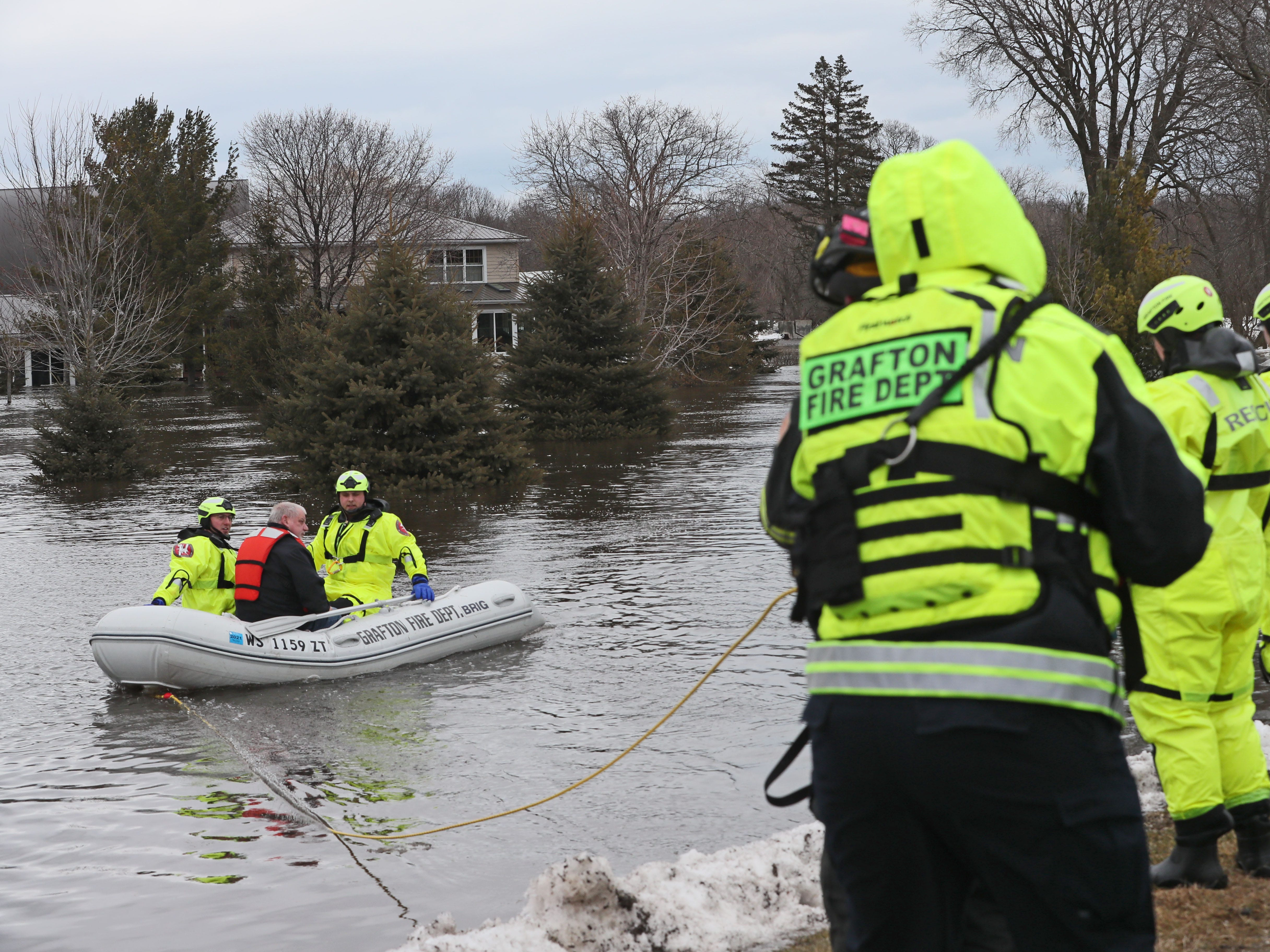 Firefighters bring a man to high ground in their boat that was rescued from the house at rear. March 15, 2019 Grafton firefighters rescued two people from the Riverview Kennel on the Milwaukee River at  1584 Pioneer Rd in Cedarburg.  Ice going out on the river was blocked by bridge diverting flow over the Cty Highway C and the surround low areas.
